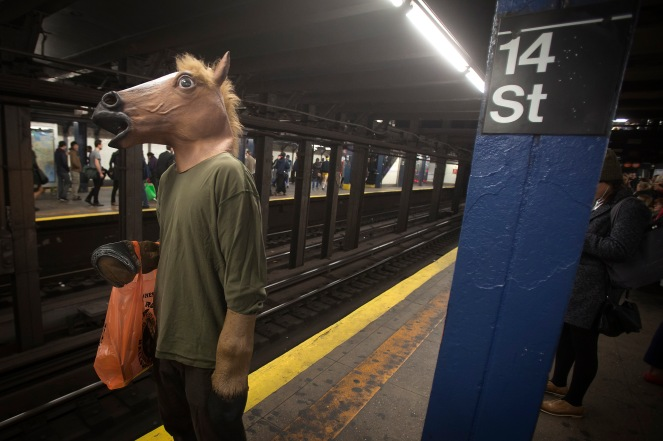 A participant in the Village Halloween Parade waits to ride the subway after the parade in the Manhattan borough of New York